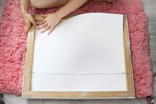 Start with a piece of canvas wall art. Cut a piece of poster board to fit inside the wood frame to give the canvas more structure and prevent your papers from showing through.