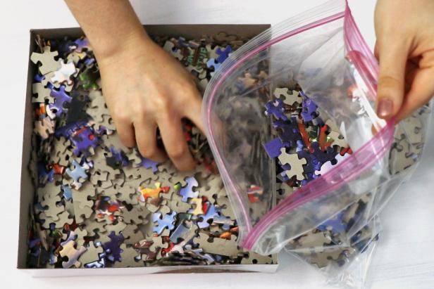 Start by transferring all of the jigsaw puzzle pieces into a large resealable bag