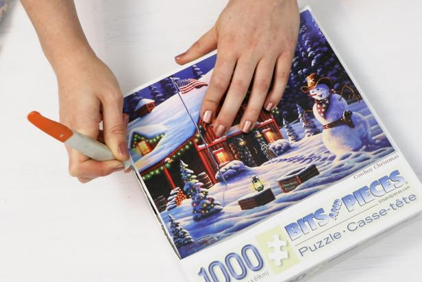 Next, use a craft knife or scissors to cut the picture from the front of the jigsaw puzzle box.