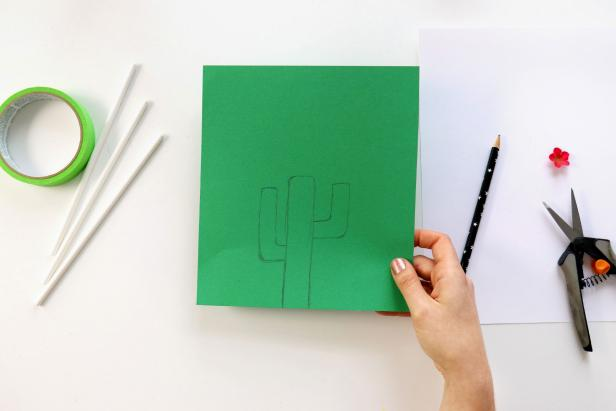 Begin by drawing a cactus shape on green paper and cut out.