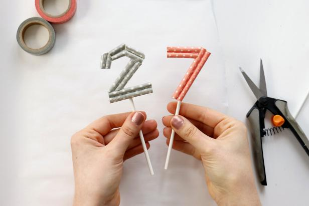 Put down parchment paper or any other non-stick surface. Use hot glue to glue all of the pieces together to form your number. Trim it as needed. Once the glue is dry, flip the number over and glue on a lollipop stick to finish.