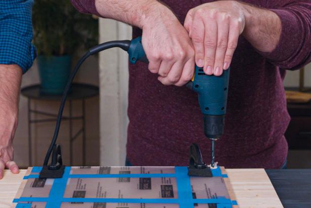 Using a drill, make holes through both the acrylic and wood at each defined pencil mark. Be sure to hold the drill firmly and press straight down. Adjust the clamps as needed.