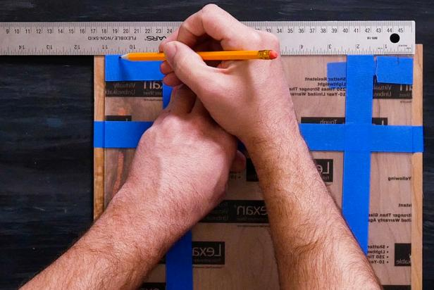 Use a ruler to center the acrylic on the wood. Then, wrap painters tape horizontally and vertically around both pieces to hold in place. Measure ½ inch from each corner and mark with a pencil.