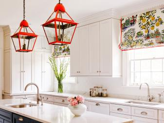 Contemporary White Kitchen with Black Island, Red Pendant Lamps and Citrus-Print Roman Shades