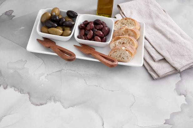 Appetizers on a white and gray watercolor-patterned countertop.