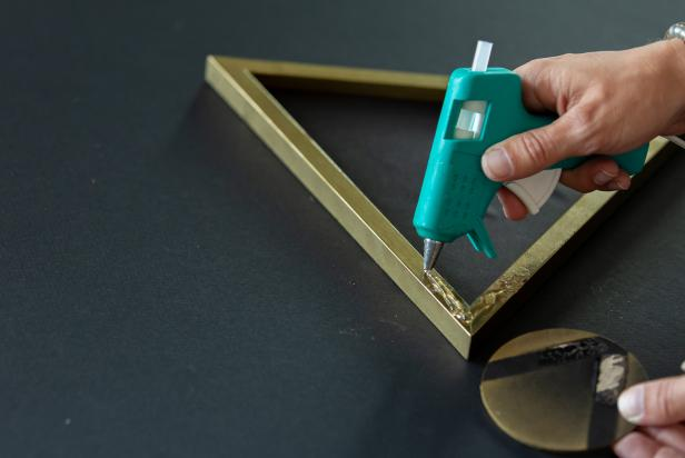 Use a low temp hot glue gun to adhere the wooden circle to the outside of the frame.