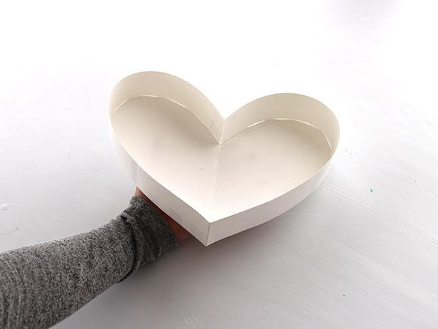 Using tape, attach the strips of paper to the edge of one of the paper hearts. Continue adding strips all the way around the edge.