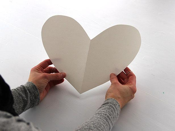Fold a piece of card stock in half, and use scissors to cut a half-heart shape along the folded edge of the paper. Unfold the paper and trim if needed.