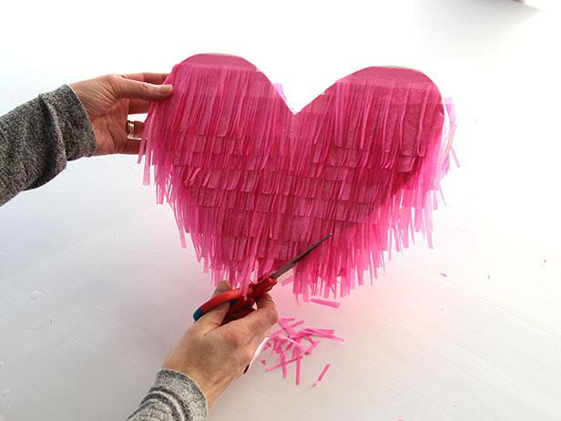 Starting at the bottom of the heart, use a glue tape roller to attach the fringe to the heart. Continue adding the fringe, layering as you go. Repeat this process on the other side. Finally, trim the edges for a neater look.