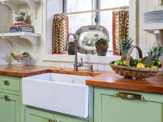 Traditional Green and White Kitchen With Farmhouse Sink and Printed Curtains